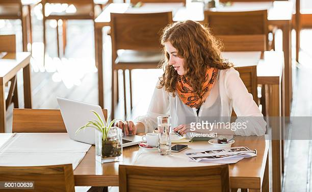 Young woman using notebook in cafe
