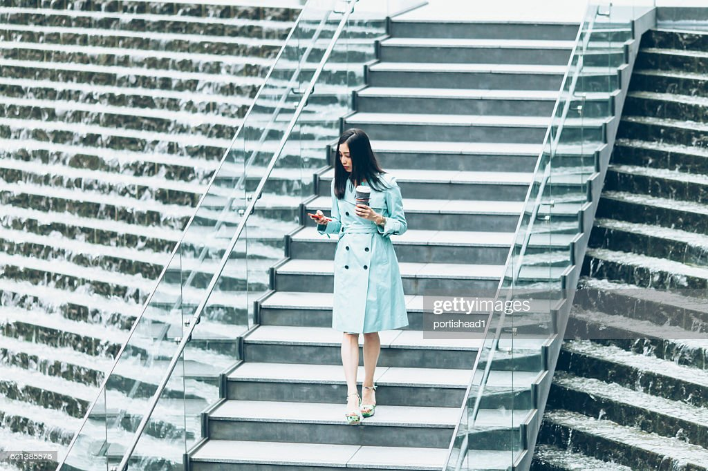 Young woman using phone and going down on stairs : Stock Photo