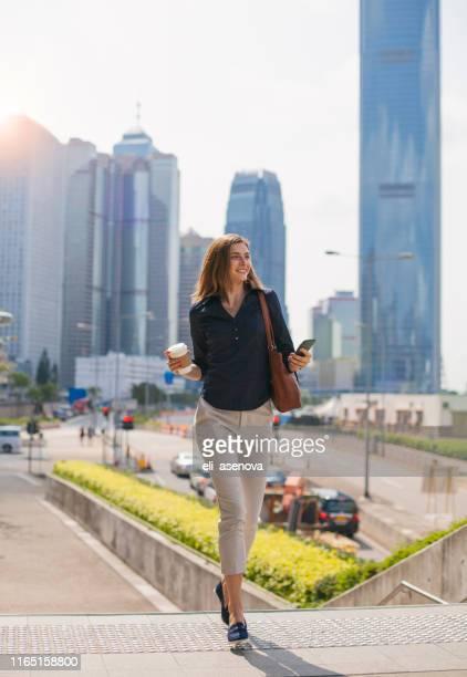 junge frau mit telefon und gehen auf treppen hong kong - bürokleidung stock-fotos und bilder