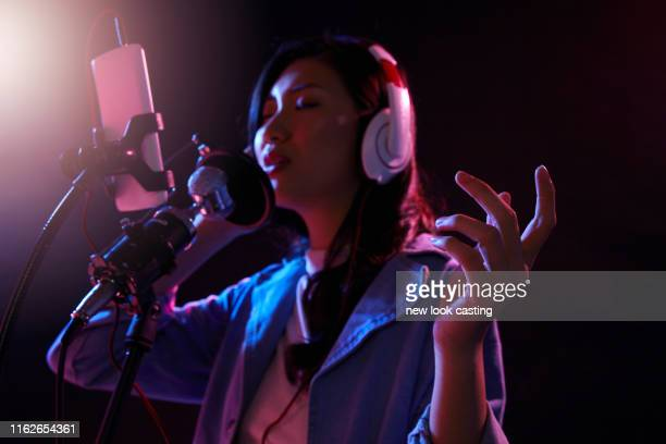 young woman using phone doing live streaming - live streaming stock pictures, royalty-free photos & images