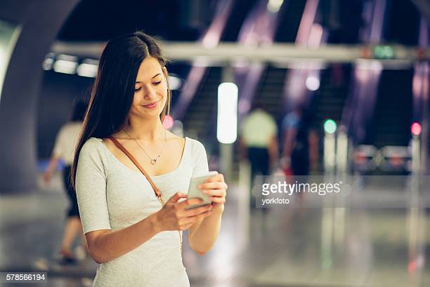 young woman using phone in Budapest subway