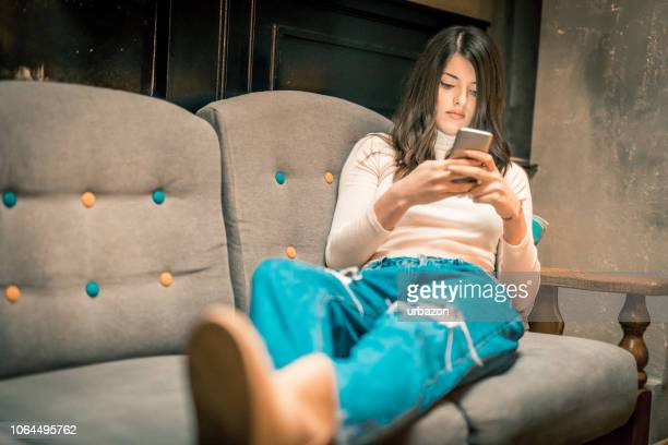 young woman using phone in downtown café - phone message stock pictures, royalty-free photos & images