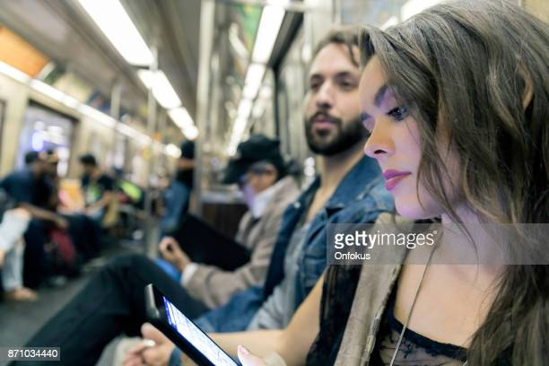 Young Woman Using phone in Subway Train, New York City
