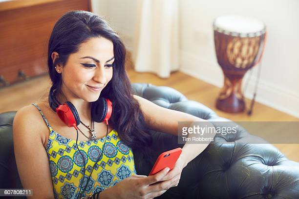 young woman using phone on sofa. - one young woman only stock pictures, royalty-free photos & images