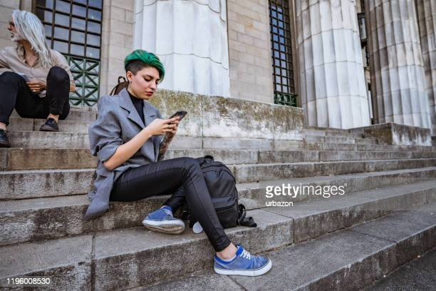 young woman using phone on stairs - green hair stock pictures, royalty-free photos & images