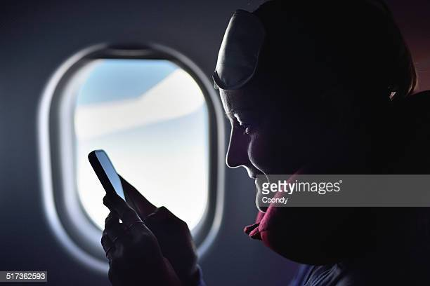 Young woman using phone on the airplane