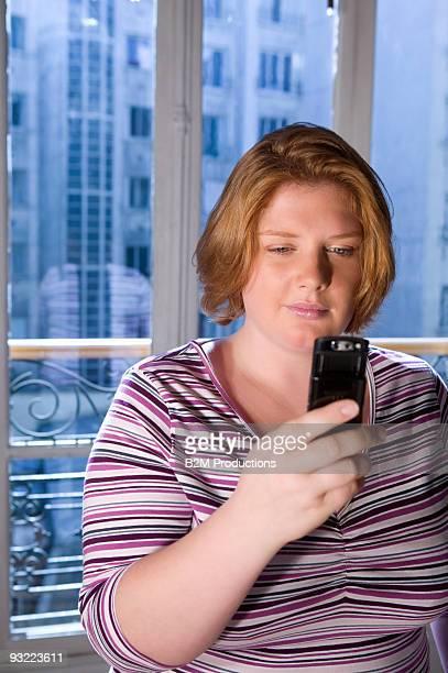 young woman using phone - blond mollig frau stock-fotos und bilder