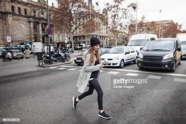 young woman using phone while crossing city street - cruzar fotografías e imágenes de stock