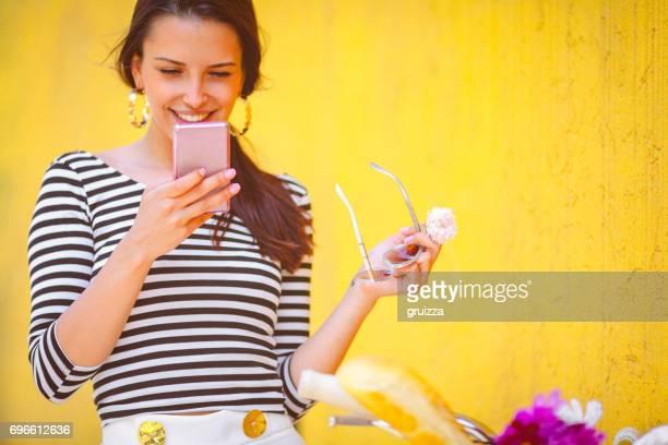 junge frau mit rosa smartphone neben dem rosa fahrrad gegen die gelbe wand - rosenfarben stock-fotos und bilder