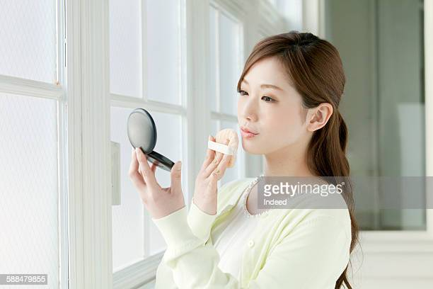 Young woman using powder puff by window