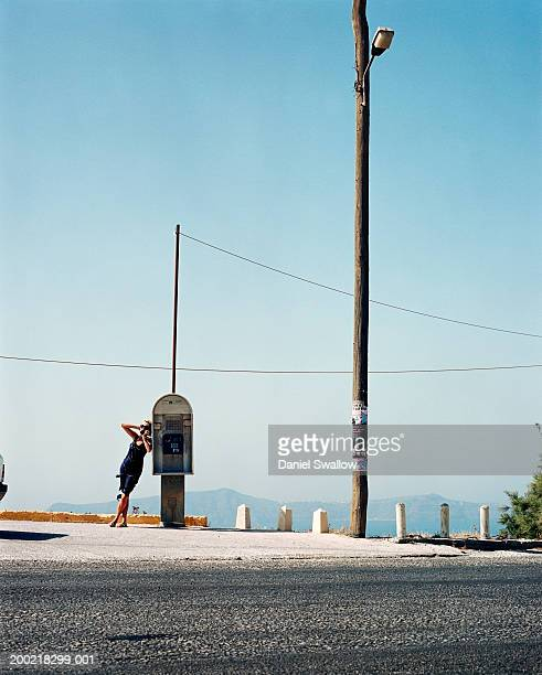 young woman using public telephone outdoors - generic location stock pictures, royalty-free photos & images