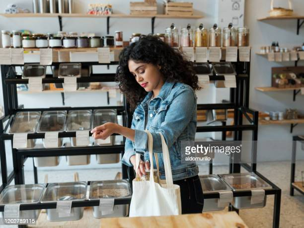 young woman using reusable shopping bag in store - organic stock pictures, royalty-free photos & images
