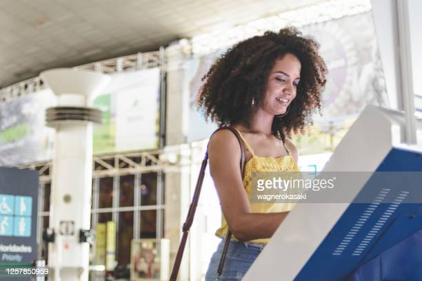 young woman using self service check in at the airport - kiosk stock pictures, royalty-free photos & images