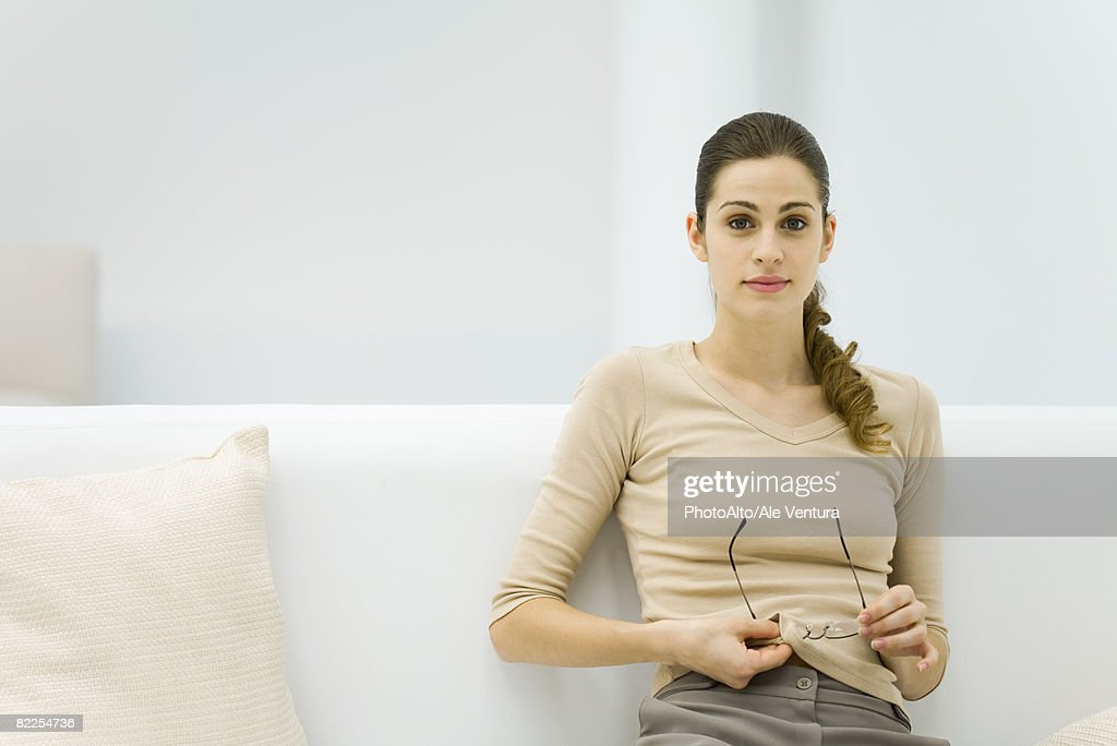 Young woman using shirt to clean glasses, looking at camera : Stock Photo