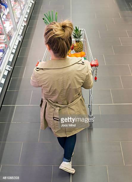 young woman using shopping trolley in supermarket