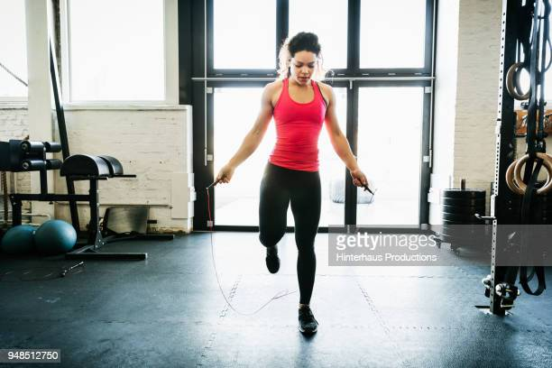 young woman using skipping rope to keep fit - skipping rope stock pictures, royalty-free photos & images