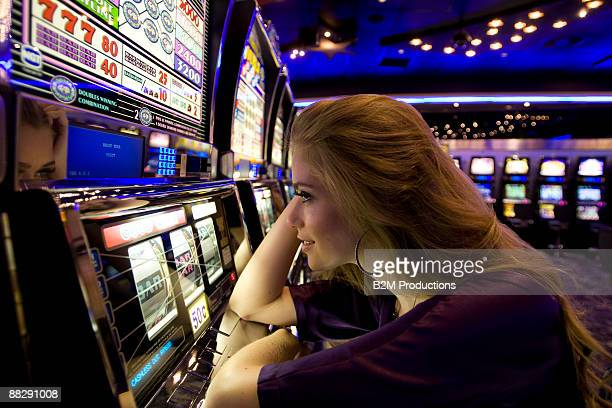 Young woman using slot machines in casino