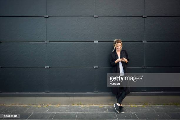 Young woman using smart phone against black wall
