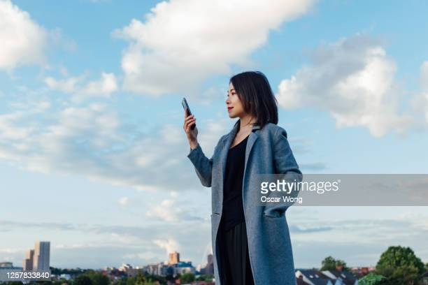 young woman using smart phone against blue sky in the city - holding stock pictures, royalty-free photos & images