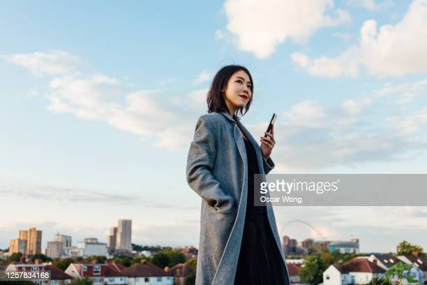 young woman using smart phone against blue sky in the city - sky stock pictures, royalty-free photos & images