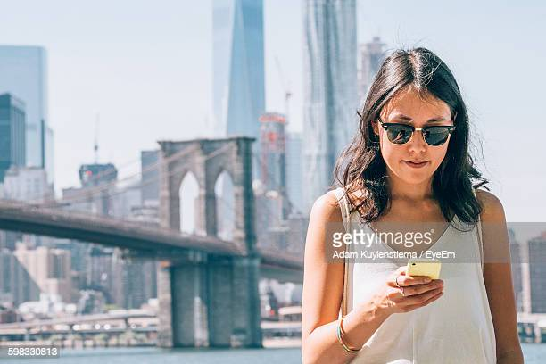 Young Woman Using Smart Phone Against Brooklyn Bridge