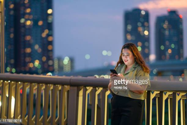 young woman using smart phone at night - plus size model stock pictures, royalty-free photos & images