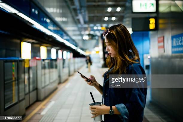 junge frau mit smartphone an u-bahn-station - izusek stock-fotos und bilder