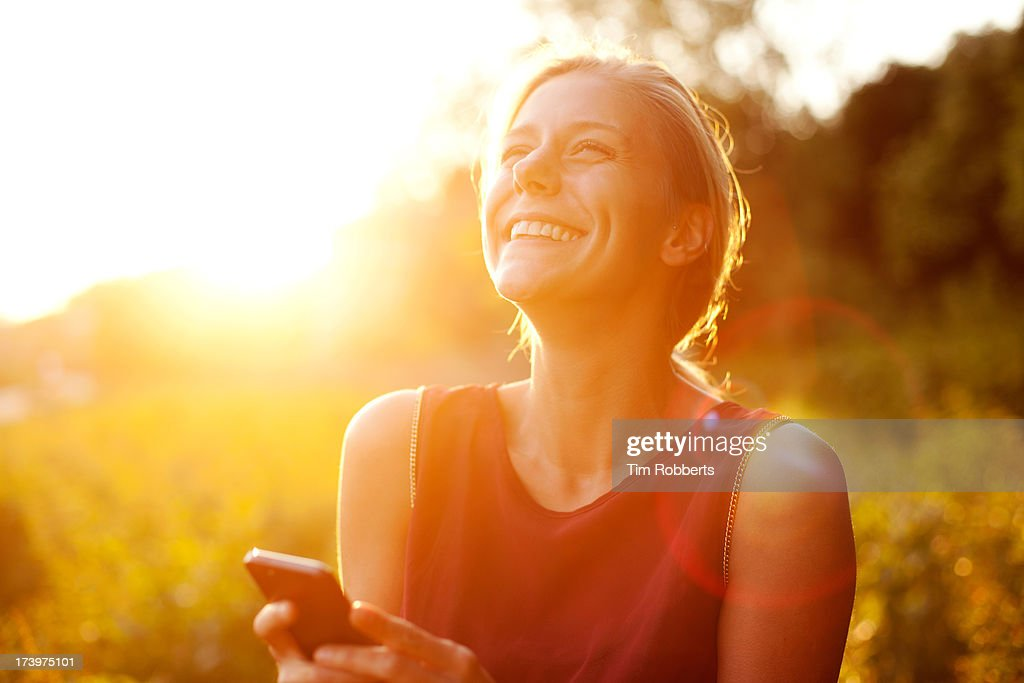 Young woman using smart phone at sunset : Stock Photo