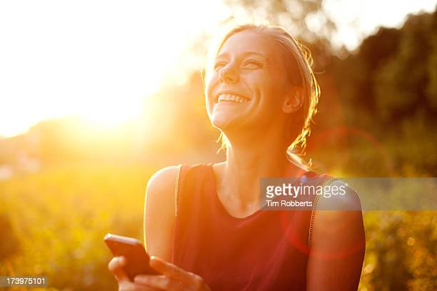 young woman using smart phone at sunset - leanincollection stock pictures, royalty-free photos & images