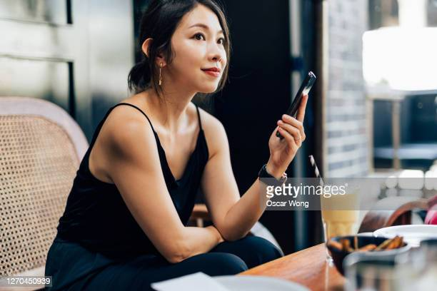 young woman using smart phone at the restaurant - east asian ethnicity stock pictures, royalty-free photos & images
