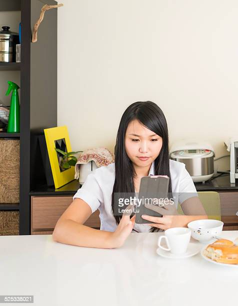 young woman using smart phone before work. - leren stock pictures, royalty-free photos & images