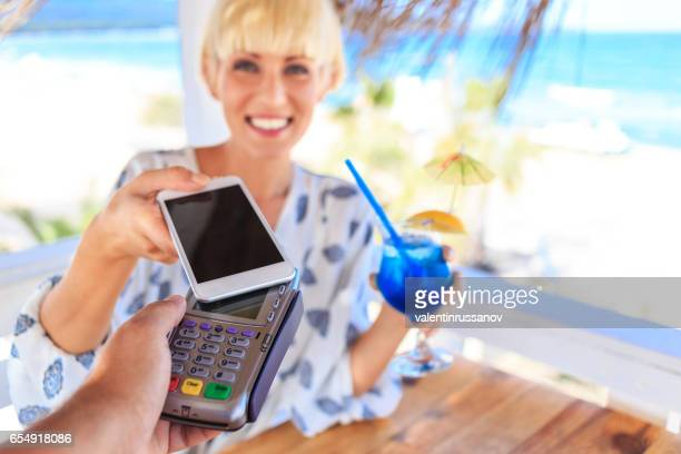 Young woman using smart phone for contactless payment on beach
