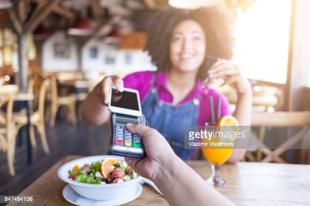 Young woman using smart phone for mobile payment