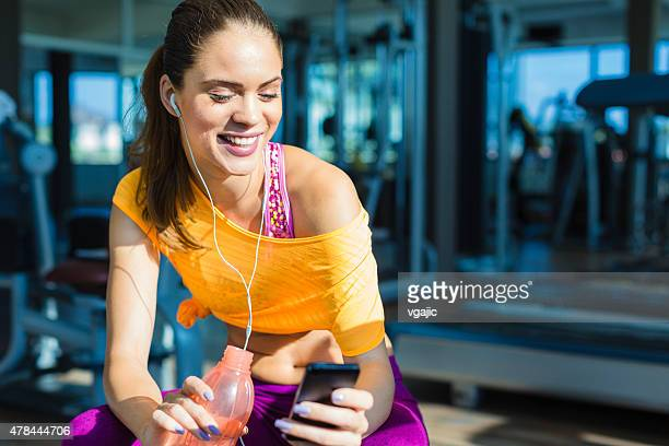 Young Woman using smart phone in a gym.
