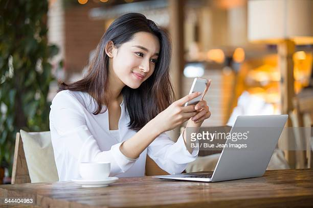 young woman using smart phone in cafe - east asia stock pictures, royalty-free photos & images