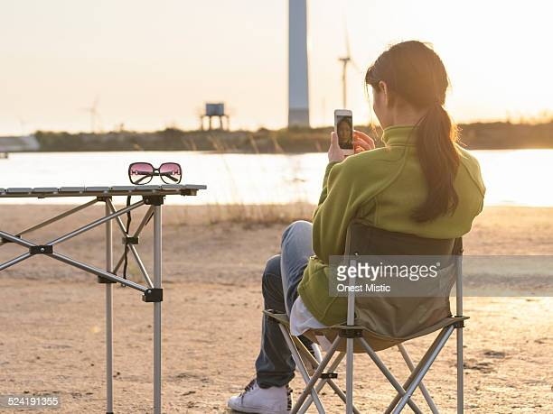 Young woman using smart phone in campsite.