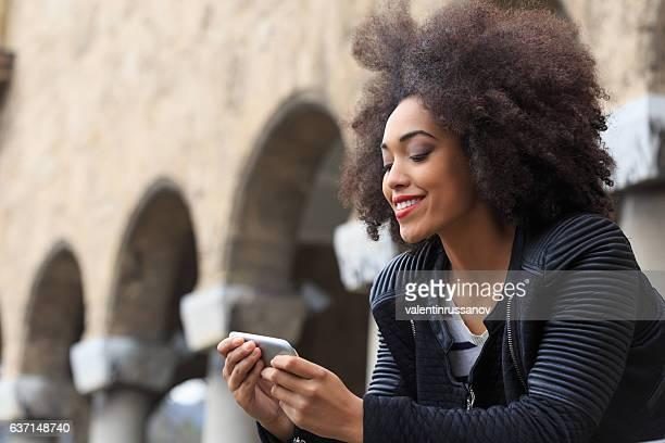 Young woman using smart phone in front of ancient columns