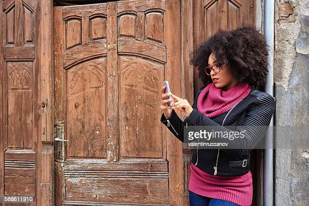 Young woman using smart phone in front of wooden door