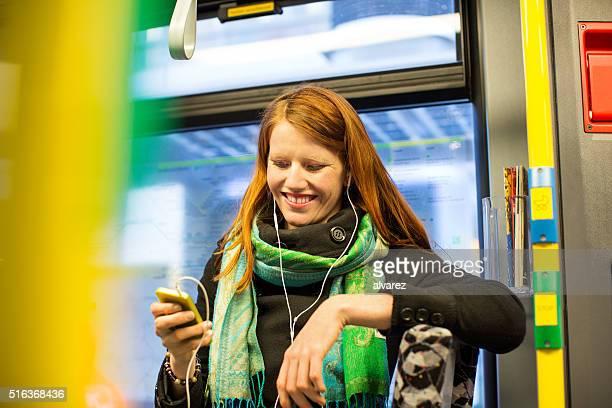 Junge Frau mit Smartphone in den öffentlichen Verkehrsmitteln