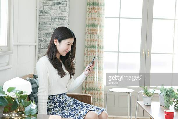 Young woman using smart phone in room