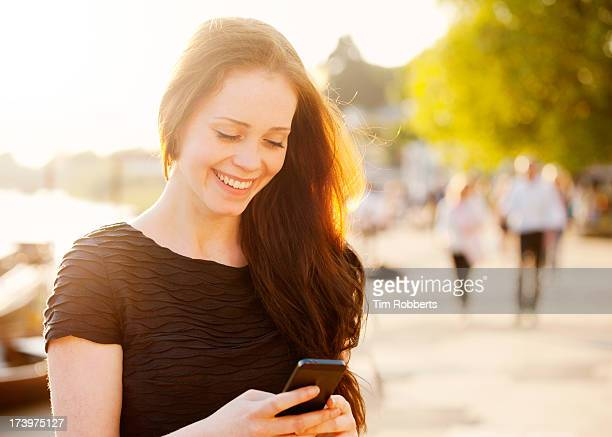 Young woman using smart phone next to river.