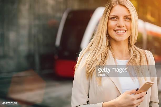 Junge Frau mit Smartphone auf der Bushaltestelle.