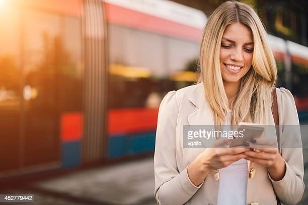 Young Woman Using Smart Phone on Bus Station.
