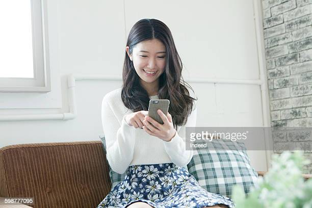 Young woman using smart phone on couch