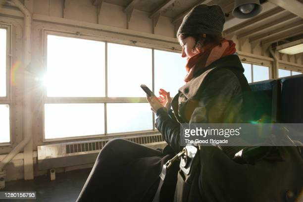 young woman using smart phone on ferry - staten island ferry stock pictures, royalty-free photos & images