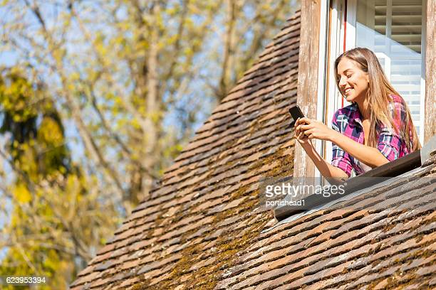 Young woman using smart phone on rooftop window