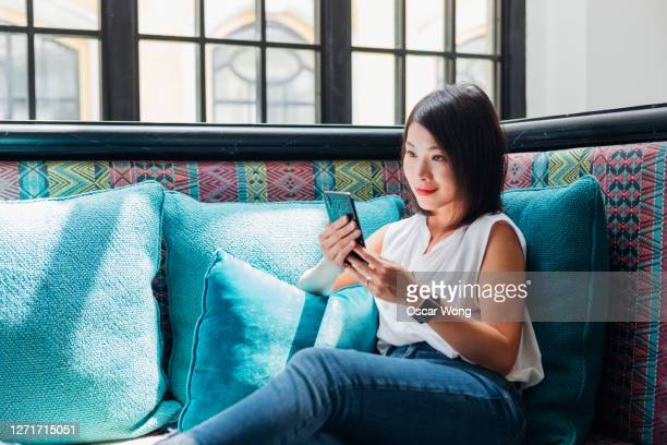 young woman using smart phone on sofa - positive emotion stock pictures, royalty-free photos & images