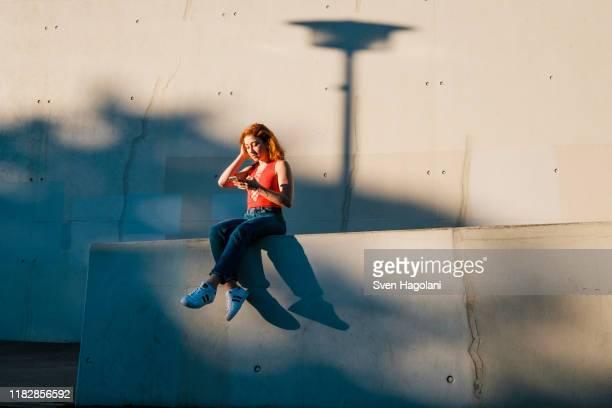 young woman using smart phone on urban wall - leben in der stadt stock-fotos und bilder