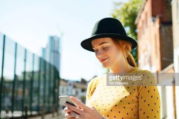 young woman using smart phone - influencer fotografías e imágenes de stock