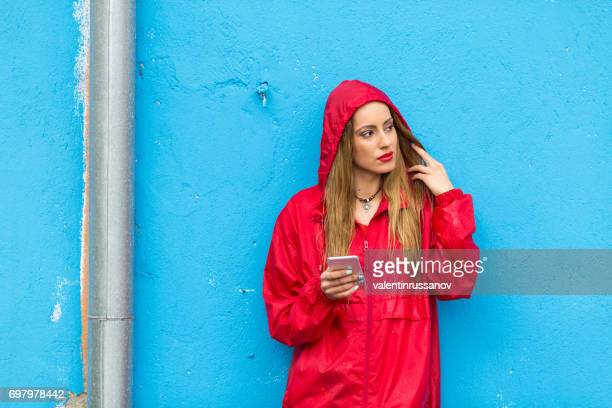 Young woman using smart phone under the rain